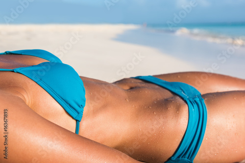 Bikini body sexy woman sunbathing on beach tanning skin of stomach and waist. Torso closeup for weight loss suntan concept.