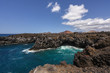 Los Hervideros lava cave in the turquoise sea with volcano in the background - the unique volcanic landscape of Lanzarote and popular touristic attraction, Canary islands, Spain