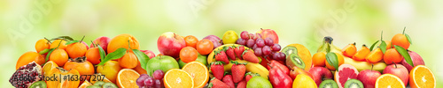 Poster Fruit Panoramic wide photo of fresh fruits for skinali on a green background.