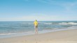 Young bald man in a yellow shirt strolls along the seacoast barefoot and enjoys herself. Beach with white sand. Outgoing coastal line. Slow Motion.