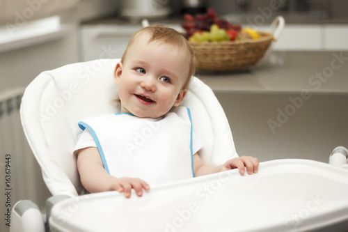 Plakat Mały chłopiec siedzi na wysokim krześle i śmiejąc się