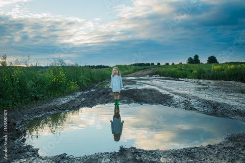 Fotografia little girl big puddle country road