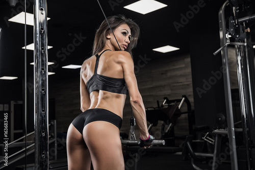 Young sexy girl in the gym. Bench triceps