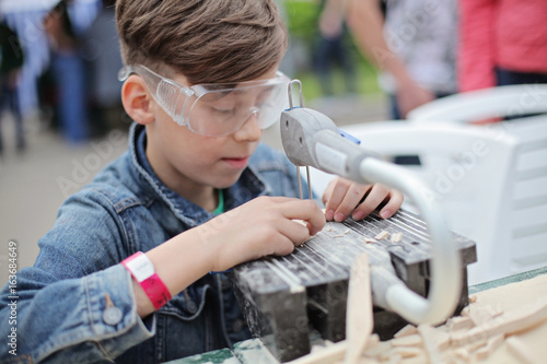 Young boy working with fret saw  Classes for young carpenter