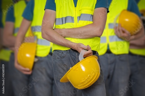 Fotografie, Obraz  Many workers in vest with protective helmet.