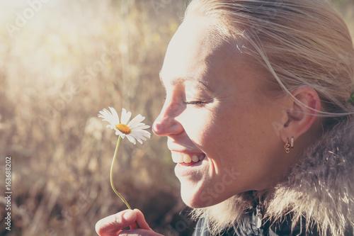 Foto  Happy woman smelling daisy flower hanging it in hands