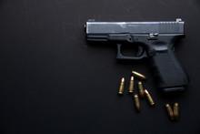Gun With Ammunition On Dark Table Background.