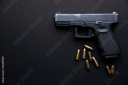 Gun with ammunition on dark table background. Canvas Print