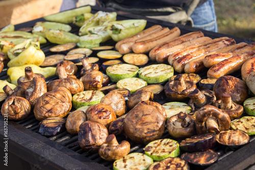 Plakat Różne pyszne grillowane mięsa z warzywami nad grilla na węglu drzewnym. Kiełbasy, stek, pieprz, pieczarki, cukinia.
