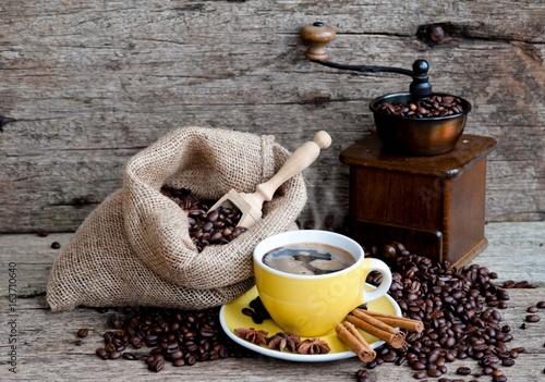 filizanka-kawy-w-zoltej-filizance-z-ziarnami-i-ciemnym-mlynkiem-w-tle