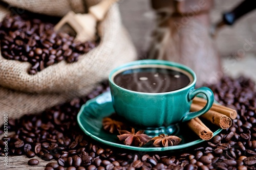 Wall Murals Cafe A cup of coffee and coffee beans on a wooden table