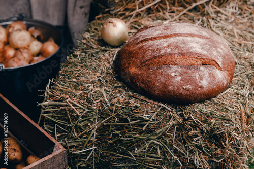 Fotomural  Peasant food in the farmer's style: baked bread, onions, potatoes on bales of hay