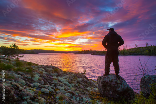 Foto op Aluminium Aubergine A man is standing on a rock. A man looks at the dawn over the lake.
