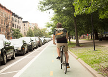 Back View Of Young Hipster Caucasian Man Riding Bike On Bike Lane