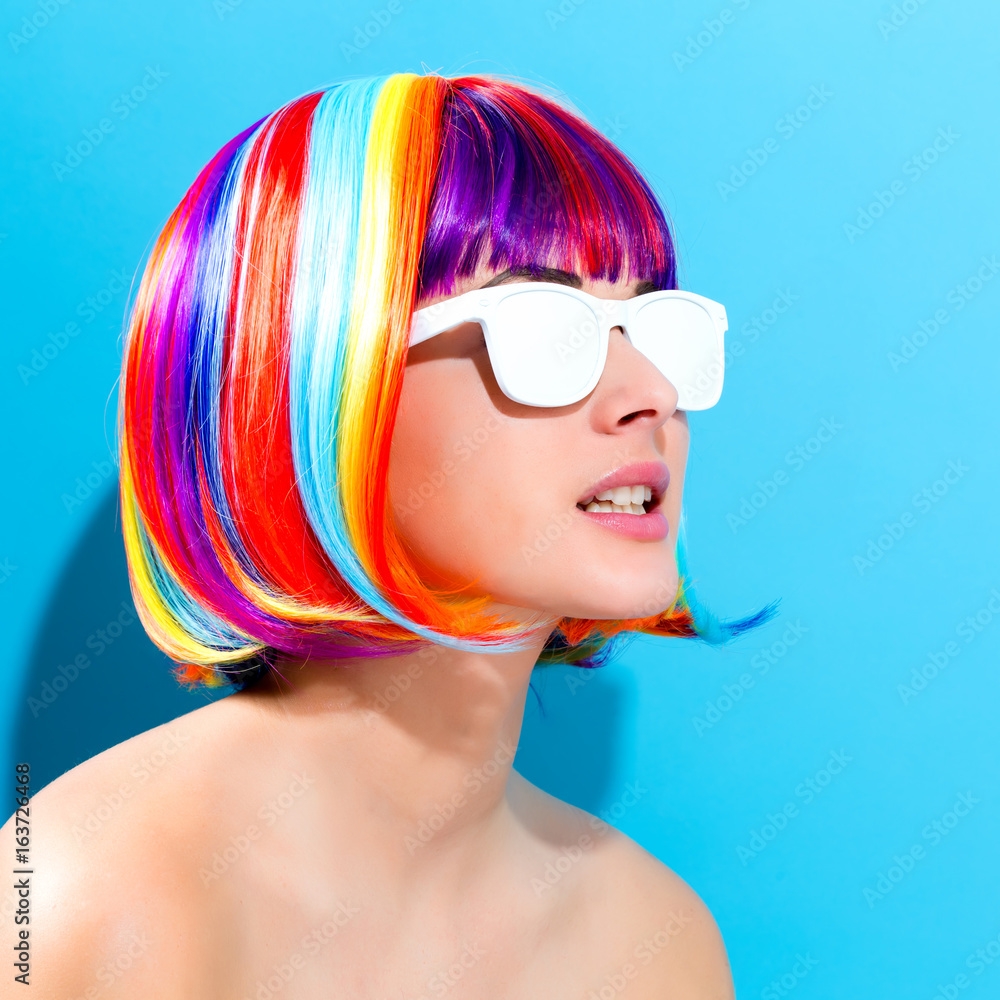 Fototapeta Beautiful woman in a colorful wig on a blue background