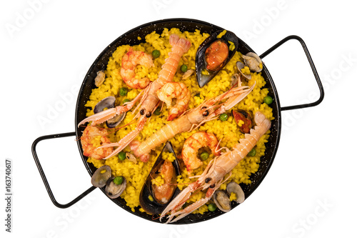 Spanish seafood paella in paellera on white background