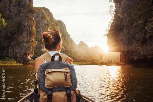 Fototapeta woman with backpack traveling by boat enjoying sunset among of mountains. obraz
