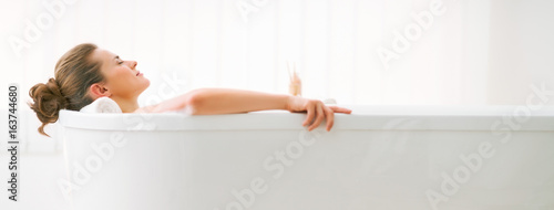 Relaxed young woman laying in bathtub Fotobehang