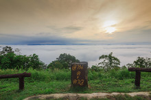 Scenery Sunrise In The Morning And Wood Sign On The Green Grass By Sea Of Mist Background. The Doi Samer Dao In Sri Nan National Park,Nan Province,Thailand