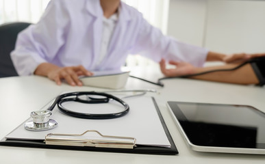 Stethoscope with clipboard and Laptop on desk, Doctor working in hospital writing a prescription, Healthcare and medical concept, test results in background