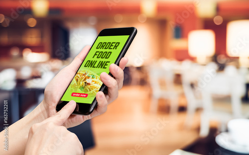 Hand holding mobile with order food online word and order now button with blur table and chair in restaurant with warm light background,Digital Lifestyle concept.