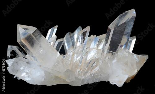 Fotografie, Obraz  A cluster of transparent Quartz crystals isolated on a black background