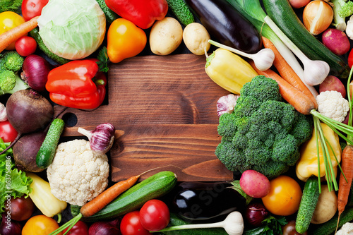 Fotobehang Groenten Autumn harvest farm vegetables, root crops and wooden cutting board top view with copy space for text. Healthy and organic food background.