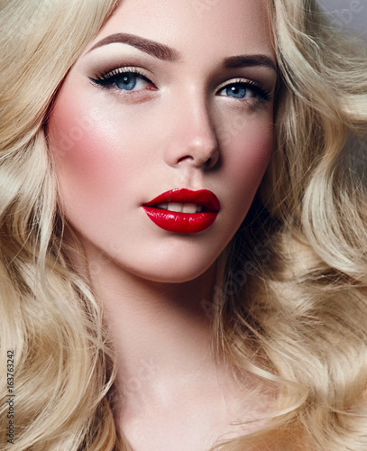 Beautiful young girl with luxurious light wavy hair close-up in the studio. Blonde - shiny, light long hair, curls. Makeup - arrows, red lipstick, ...