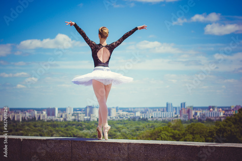 Fotografie, Obraz  Ballet dancer in white tutu posing in city near garden