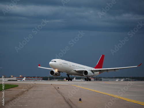 Poster Avion à Moteur Airplane on the runway in the background of a rainy sky