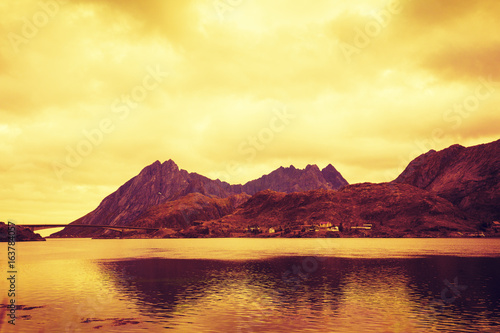 Fotobehang Zwavel geel Mountains by the sea at sunset. The beautiful nature of Norway