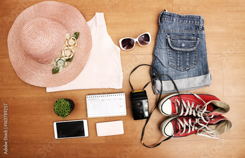 1034bfcc51d0 flat lay feminine clothes and accessories collage with shirt, jeans shorts,  sunglasses, bracelet