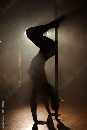 Obrazy na płótnie Canvas Young sexy woman exercise pole dance on a dark background