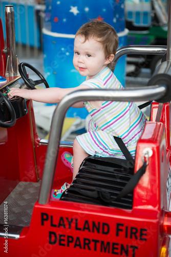 Fotografie, Obraz  Young toddler girl riding on boardwalk amusement ride