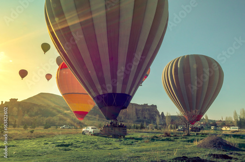 Hot air balloons landing at sunrise in sun beams after flying in the valley of Goreme.