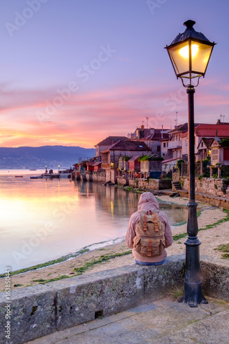 tourist sitting on his back at sunrise in the town of Combarro, Pontevedra, Galicia, Spain