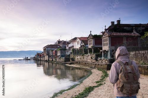 tourist walking along the seashore in the town of Combarro, Pontevedra, Galicia, Spain