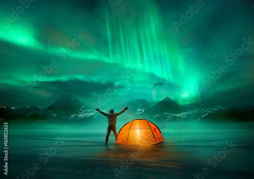 Fotobehang Noorderlicht A man camping in wild northern mountains with an illuminated tent viewing a spectacular green northern lights aurora display. Photo composition.