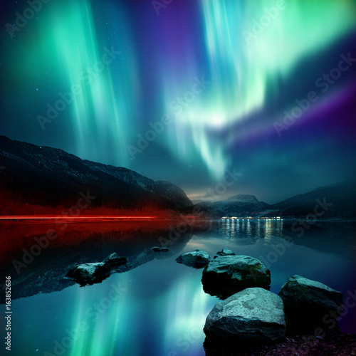 Keuken foto achterwand Noorderlicht A large Northern Lights (aurora borealis) display glowing over a mountain pass and reflected on a lake at night. Photo composition.