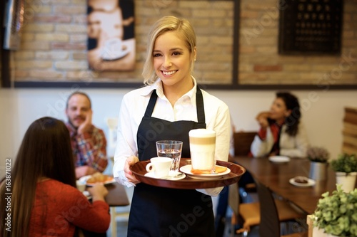 Fotomural  Happy waitress holding tray