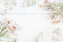 Flowers Composition. Floral Frame Made Of Pink Gypsophila Flowers And Daisy Flowers On White Wooden Background. Flat Lay, Top View, Copy Space