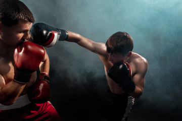 Fototapeta na wymiar Two professional boxer boxing on black smoky background,