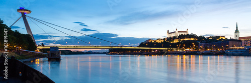 Bratislava, New Bridge, Castle, Cathedral during dusk from a boat on river Danub Poster