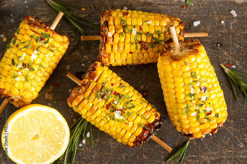 Fototapeta Corn grilled with salt and spices. Dark background. Fast food in the summer. obraz