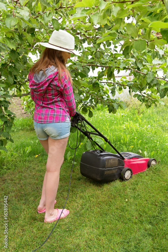 A young teenage girl in a jeans shorts shirt and a straw hat mowing ...