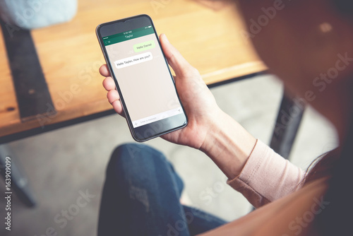 Fotografía  Social network, Chating and messaging concept, Closeup woman hand holding smart phone, Mock up to screen chat box