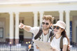 Happy couple or partner tourism are sightseeing city with map, man pointing to copy space. Or lover backpacker travel with honeymoon trip in holiday vacation together concept.