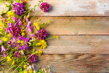 Wildflowers On A Wooden Rustic Vintage Background With Space For Text