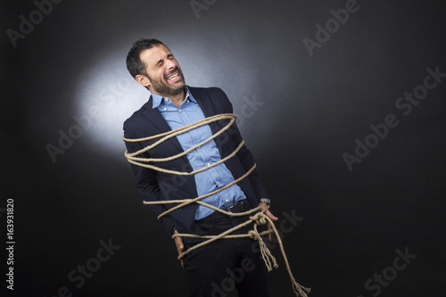 Uomo con giacca e camicia legato da un fune è disperato perché non può muoversi Slika na platnu