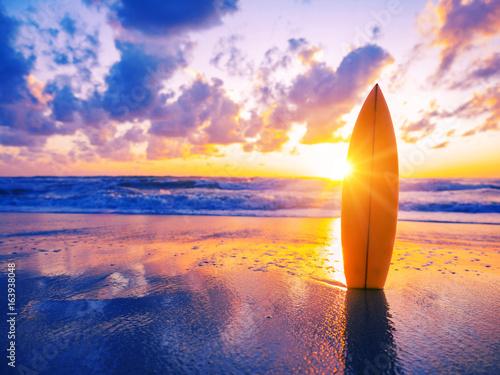 Plakat Deska surfingowa na plaży o zachodzie słońca